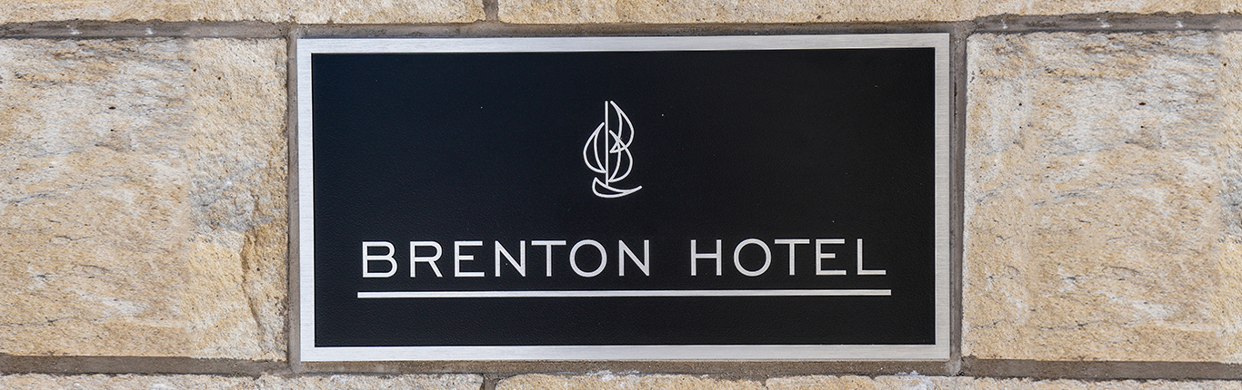 exterior building metal sign of navy blue and etched with brenton hotel boat icon and logo