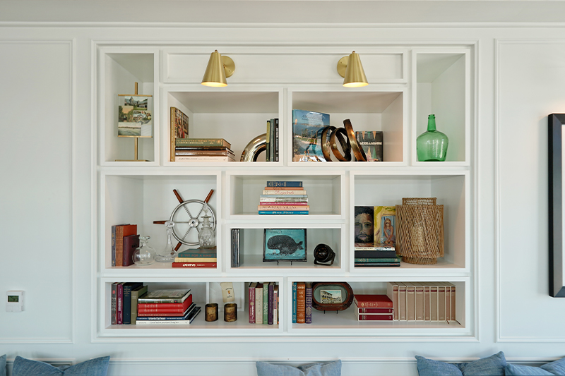 white built-in bookcase with books, ship wheel decor and sea glass vase